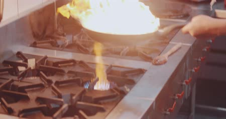 Chef fires up the flambe on a hot pan . Slow motion of chef cooking in the kitchen