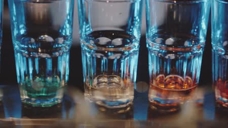 dyskoteka : Slow motion pan across glasses with different colors spirits on the bar in night club