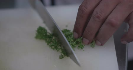 saŁata : Slow motion closeup of man hands cutting fresh parsley in the restaurant kitchen