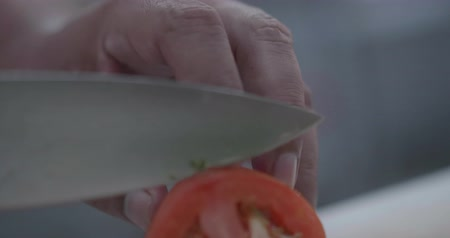 rijp : Slow motion closeup of man hands cutting tomato in the restaurant kitchen