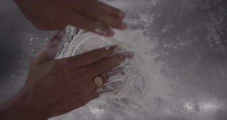 trouba : Slow motion closeup of male hands kneading pizza dough with flour in the restaurant kitchen