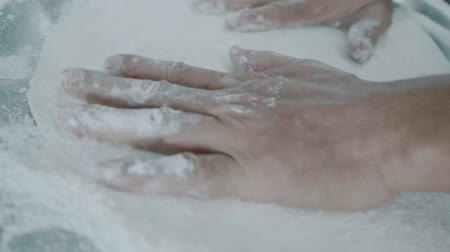 fatia : Slow motion closeup of male hands kneading pizza dough with flour in the restaurant kitchen