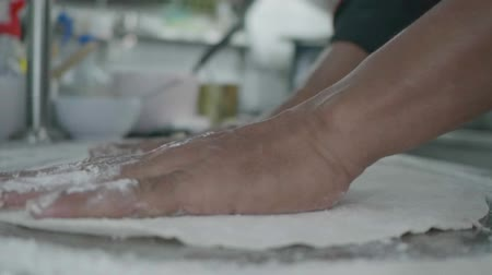 Slow motion closeup of male hands kneading pizza dough with flour in the restaurant kitchen