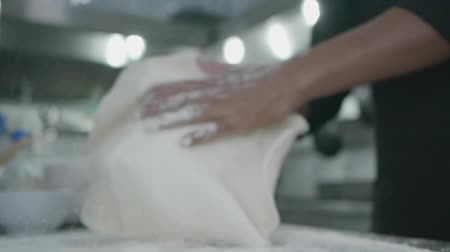 parsley : Slow motion closeup of male hands kneading pizza dough with flour in the restaurant kitchen