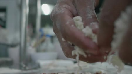trouba : Slow motion closeup of male hands sprinkles cheese on the pizza in the restaurant kitchen