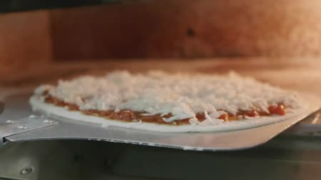 jíst : Slow motion closeup chef putting pizza to the oven in the restaurant kitchen