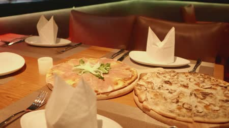 ветчина : Slow motion freshly baked pizzas served on the table in the restaurant