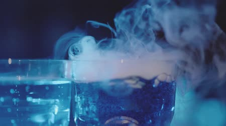 Slow motion glasses and steam from dry ice on the bar in the night club