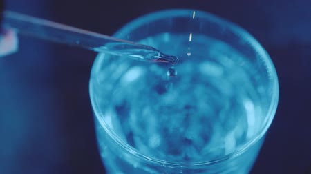 Slow motion top view closeup of liquid drop from laboratory pipette to the glass with water