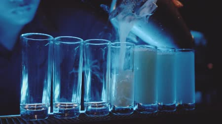 pálinka : Slow motion shots being poured with dry ice steam on the bar in the night club
