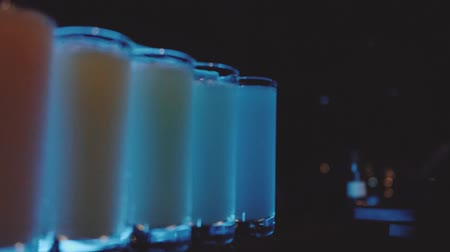 dyskoteka : Slow motion pan across shot glasses with different colors spirits on the bar in night club Wideo