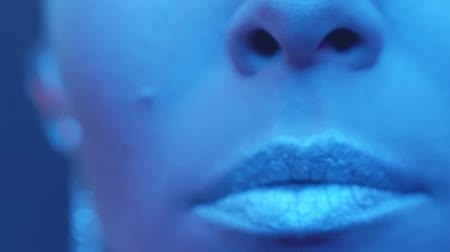 vibráló : Slow motion closeup woman lips with metallic lipstick smoking in the night club