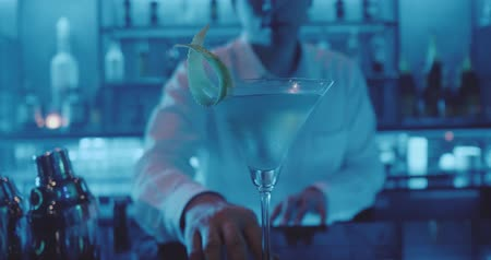 дух : Slow motion blurred image of barman giving away the cocktail in the night club. Closeup female hand receiving drink from bartender