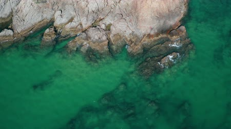 открытка : Aerial drone top view of turquoise sea surface with stones and rocks in water Стоковые видеозаписи