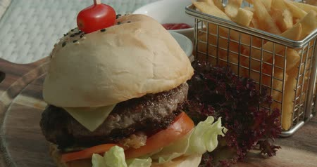 saŁata : Classic burger with french fries in small fry basket on wooden cutting board