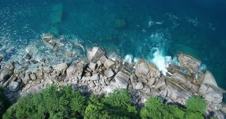 formação rochosa : Aerial drone top view of turquoise sea surface with stones and rocks in water Stock Footage