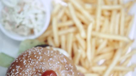 american cuisine : Top view of burger with french fries and coleslaw - video in slow motion