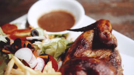 saŁata : Roasted half chicken with crispy golden brown skin served with fresh salad and french fries - video in slow motion