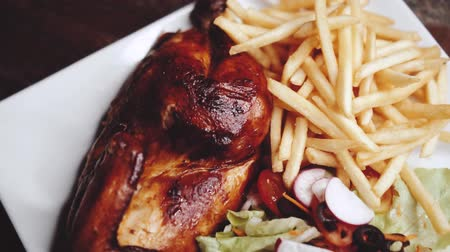 batatas fritas : Roasted half chicken with crispy golden brown skin served with fresh salad and french fries - video in slow motion