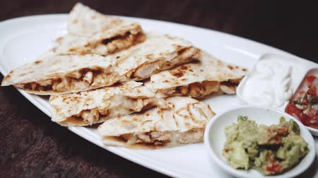 рекламный : Sliced chicken and cheese quesadilla served with guacamole, pico de gallo and sour cream dip - video in slow motion