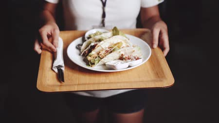 рекламный : Closeup female hands serving chicken and cheese and beef tacos served with guacamole, pico de gallo and sour cream dip - video in slow motion