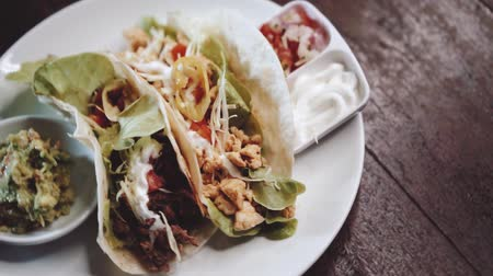 taco : Chicken and cheese and beef tacos served with guacamole, pico de gallo and sour cream dip - video in slow motion Stock Footage