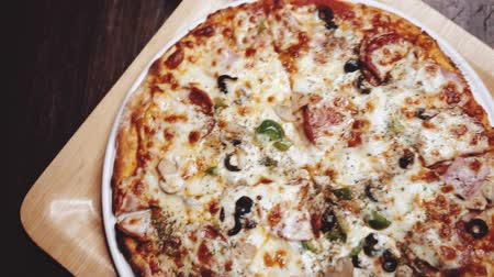 trouba : Top view closeup of freshly baked super supreme pizza in restaurant - video in slow motion