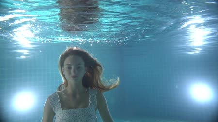respiração : Beautiful woman with long red hair swimming underwater in dress - video in slow motion