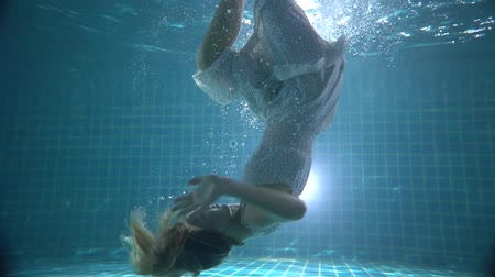 mermaid : Beautiful woman with long red hair swimming underwater in dress - video in slow motion