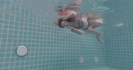respiração : Beautiful woman with long red hair posing underwater in bikini - video in slow motion Vídeos