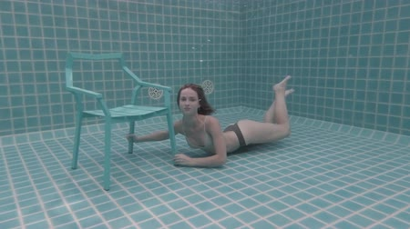 respiração : Beautiful woman with long red hair posing underwater on the chair - video in slow motion Vídeos