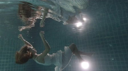 dech : Beautiful woman with long red hair swimming underwater in dress - video in slow motion