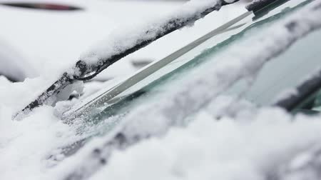wipe away : wipers brushing away snow from a cars windshield