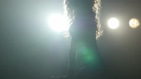 striptérka : Silhouette of a girl dancing on the background lights. Slow motion