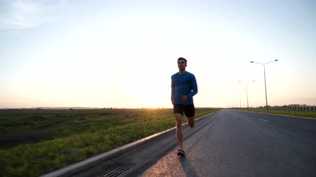 atlet : The guy runs along the road at sunset. Front view