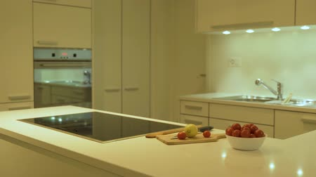 kvarc : Prospective view of the kitchen base cabinets, kitchen doors and drawers are made of the flat wood panels in white color. As a kitchen design concept quartz countertops are decorated with the plates and food.