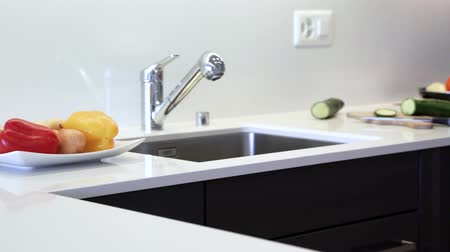 kuvars : Countertop made of the modern quartz slab. Kitchen counter is made in white color with chrome sink and faucet. Kitchen cabinets are made of modern black flat panels. Stok Video