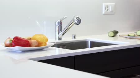 kuvars : Kitchen countertop made of the granite slab. Counter is made in modern white color with chrome sink and faucet. Kitchen cabinets are made of black flat panels. Stok Video