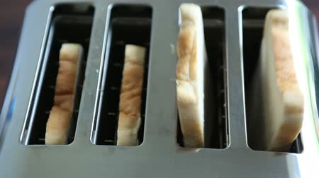 kahvaltı : Freshly sliced bread popping up from a modern toaster at breakfast time. Stok Video