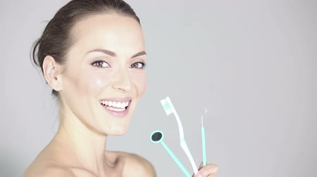 зубы : Beautiful young woman holding a toothbrush mirror and dental scraper smiling and laughing in a health and beauty style pose while in profile