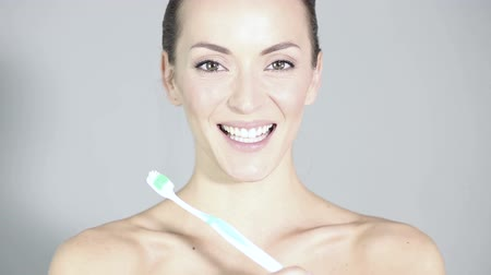 dış : Beautiful young woman holding a toothbrush smiling and laughing in a health and beauty style pose