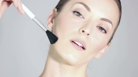 okşayarak : Beautiful young woman holding a make up brush and stroking her face in a health and beauty style pose Stok Video
