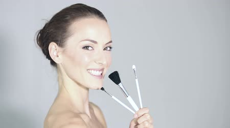 уход за кожей : Beautiful young woman holding a selection of three make up brushes in profile