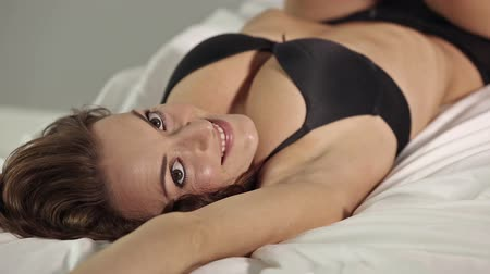 almofada : Beautiful young woman rolling over and stretching in her bed smiling and relaxing in underwear Vídeos