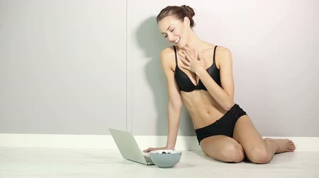 mordendo : Beautiful young woman using her laptop on the floor laughing in underwear at home