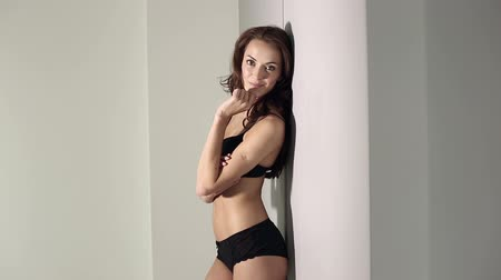 pansuman : Beautiful young woman standing against her bedroom wall in black underwear smiling