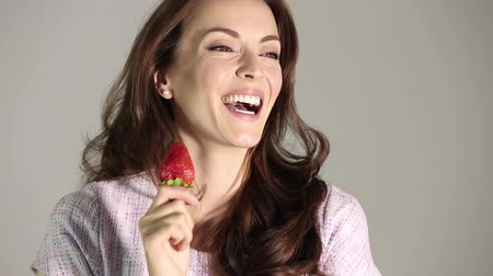 смеющийся : Beautiful young woman in a purple dress laughing and holding a fresh strawberry