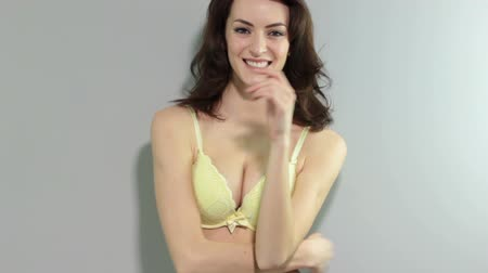 bra : Beautiful young woman in a yellow bra smiling and relaxing