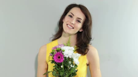 único : Young woman holding a bouquet of flowers smiling and waiting for someone