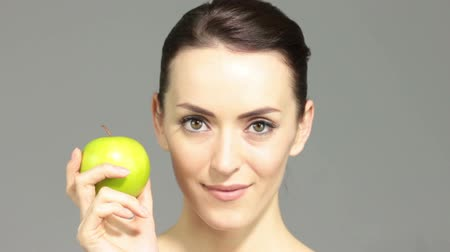 estilo de vida saudável : Beautiful young woman holding an apple in a beauty style pose smiling Vídeos